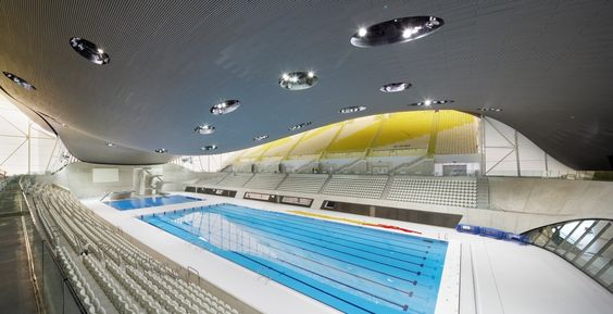 Installée à Londres depuis la fin des années 1970, Zaha Hadid réalise le centre aquatique qui accueille les Jeux olympiques à l'été 2012. «Bien sûr, l'idée de la vague était une évidence, confiait-elle alors au Huffington Post. Ensuite, il a fallu nous intéresser à comment l'intégrer au paysage et la traduire en terme d'architecture.» Le bâtiment était u...