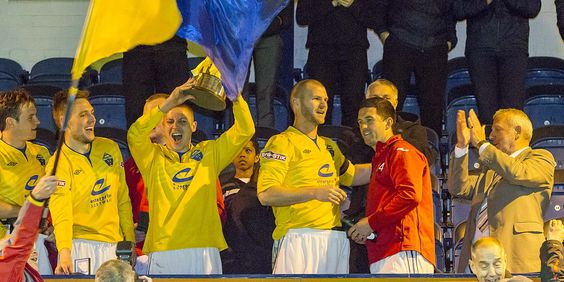 Scott Metcalfe lifts the Doodson Sports Cup with Warrington Town FC
