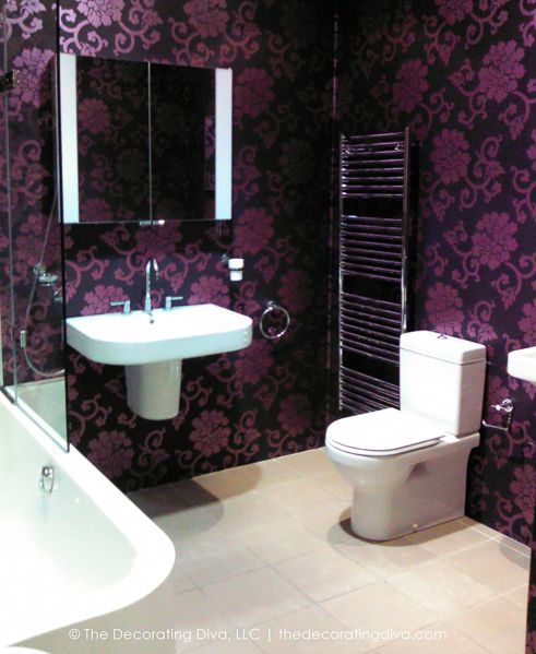 Elegant and modern bathroom in white with purple and black brocade paper | The Decorating Diva, LLC