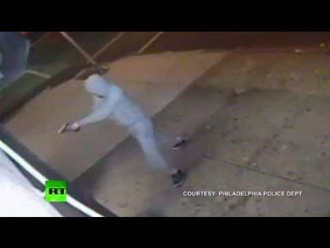 Video courtesy: Philadelphia police dept  Philadelphia police are still trying to find a man who fired into an Asian food store and wounded three people on Tuesday night. Several young men scrambled to hold the door shut from inside. The gunman was able to push open the door far enough to fire several shots, wounding three of the men inside.  The...