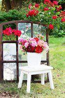 Dahlienstrauss auf Hocker im Garten