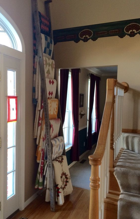 I spent time arranging my oldest quilts on my ladder yesterday. Our foyer is two stories tall and has the stairway in it. I was able to tilt the ten foot ladder towards the first landing to place t…