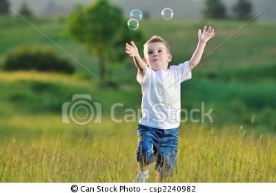 by dotshock (happy young beautiful child have fun on eadow with soap bubbles toy)