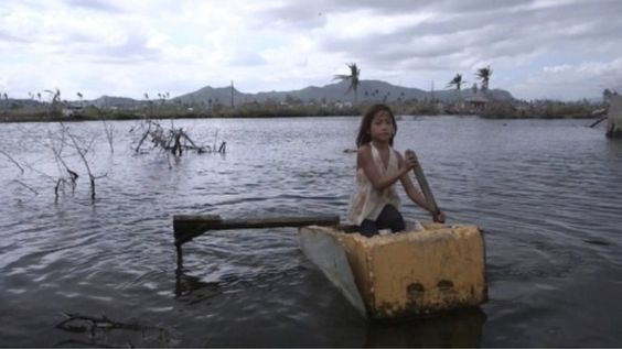Rose, 9, uses an upturned refrigerator as a small paddle boat Photo: Mark Bushnell/Oxfam