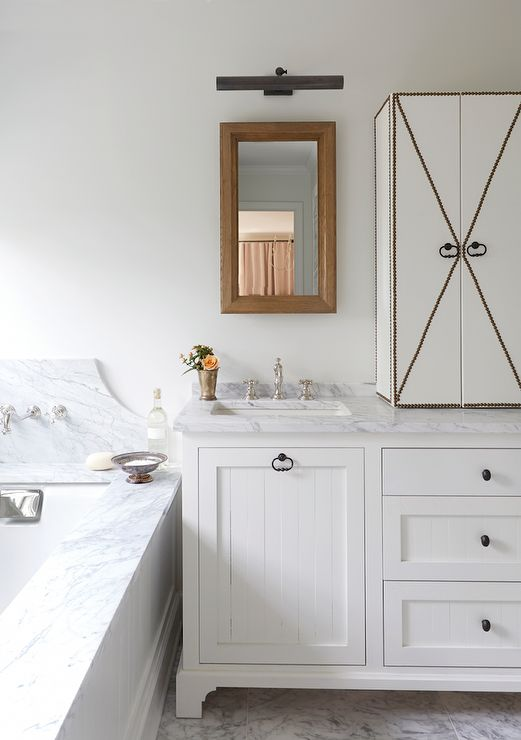 Cottage Bathroom Features A White Vanity Accented With White Beadboard Doors Adorned With Oil
