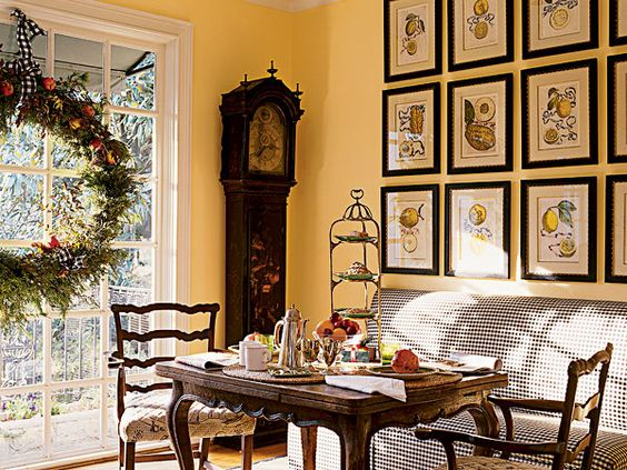 An oversized wreath adorned with fruit creates a focal point on this wall of windows in the breakfast nook. (Photo: Tria Giovan)
