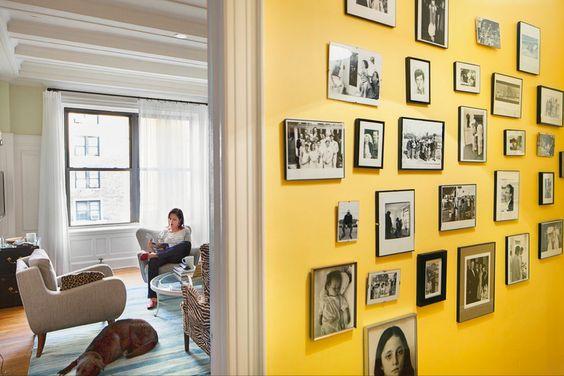 yellow wall with black & white photos, via nytimes