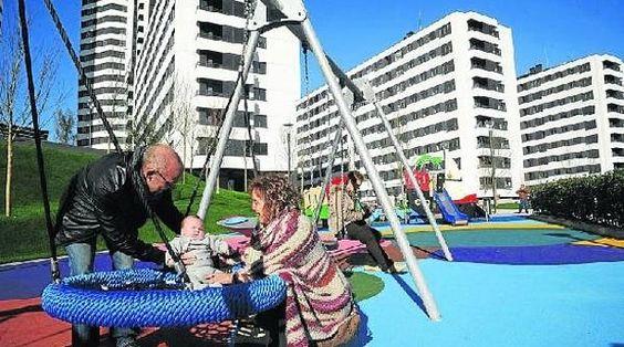 Una pareja juega con su hijo en los columpios del nuevo parque de Garellano, urbanizado por Ría 2000 y donde en breve se venderá un nuevo solar para pisos.
