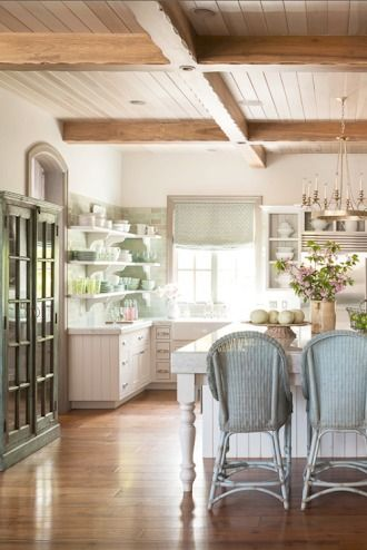Natural light streams into a French Country kitchen with warm wood ceiling, white cabinetry, antique cabinet, open shelving, and aqua tile and accents. Decor de Provence.