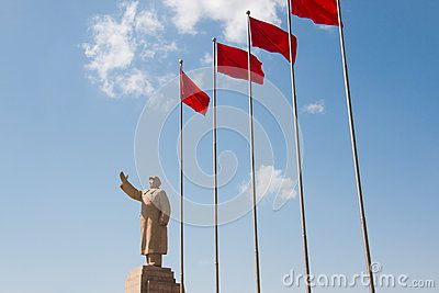 Chairman Mao stone statue waving in front of blue sky and a white cloud with red flags next to him
