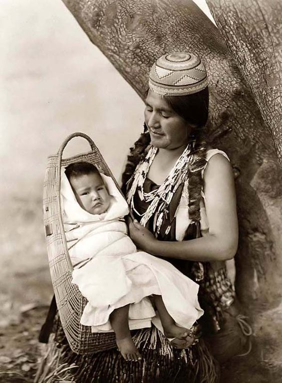Here for your consideration is an aesthetic picture of a Hupa Mother and Baby in a Three-quarter Length Portrait. It was created in 1923 by Edward S. Curtis.    The photograph presents a touching image of this Mother and Child. There is a look of pride in this woman's eye as she gazes at this child.    We have created this collection of illustrations primarily to serve as a valuable educational tool. Contact curator@old-picture.com.    Image ID# EB76758D: