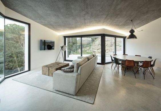Con una palette cromatica neutra, virante ai toni del grigio, l'interno della villa catalana è arredato utilizzando mobili disegnati su misura e realizzati con materiali di recupero. Unico tocco design, la seduta DWS di Charles Eames, in versione nera