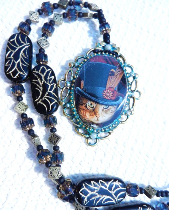 Steapunk Victorian Cat in Top Hat Pendant Necklace with hand painted, tarnished patina & faux pearl accents, glass & vintage cut glass, metal beads w cut glass in blue, black & gold / brass, strung on 24 inch ribbon with adjustable knot. Hand painted, one of a kind. Perfect for Cosplay.