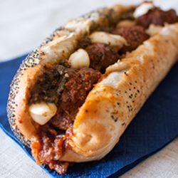 Meatball sandwich with mozzarella and basil pesto.