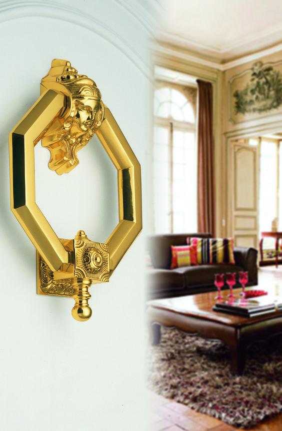 Es un llamador de aro con la cara de mujer en tono pulido brillo, dorado sobre una puerta lacada en blanco. Le dará un estilo sofisticado y elegante a su puerta de entrada.
