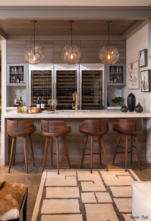 A gorgeous basement bar with tile floors, a wood backsplash and plenty of seating. The beautiful pendant lighting makes the whole room come together! Click to see 10 creative lighting trends for your home.