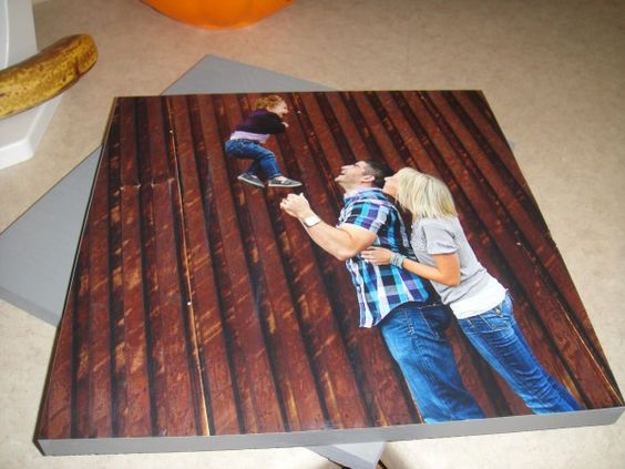 Go to Lowes and buy the cheapest board they have (12″ x 36″) I believe it is around $6.50 for the board, and you can pay .25 a cut at Lowes as well. I had them cut the board into three equal parts (12″ x 12″). Pick up Mod Podge as well, and some sponge brushes. Develop pictures at Costco for $2.99 a picture! (12″ x 12″) First step is to paint the boards. ~ I painted the whole back and the sides grey. Just use left over house paint. ~ Next you let the paint dr...