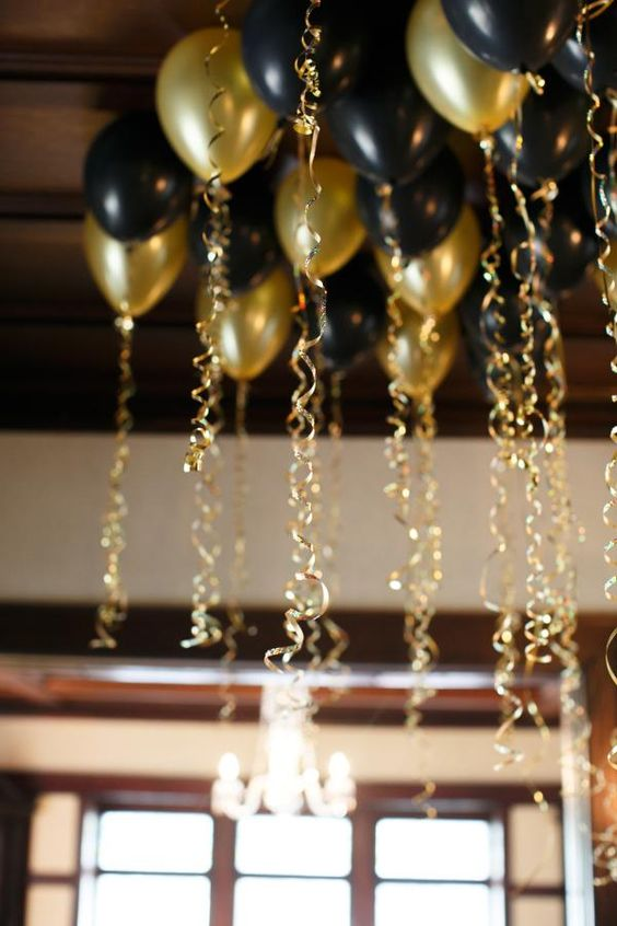 8 incredible New Year's Eve Party Decoration Ideas - black and gold balloons with gold ribbon