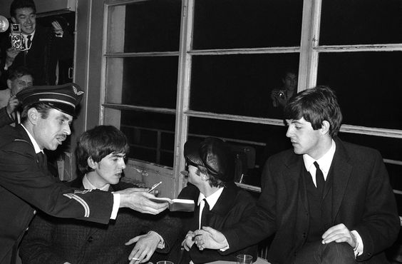 Members of the Beatles John Lennon; George Harrison; and Paul McCartney, about to sign an autograph, after arriving in Paris, France for a series of concerts at L'Olympia on Jan. 14, 1964. (AP Photo/Spartaco Bodini)