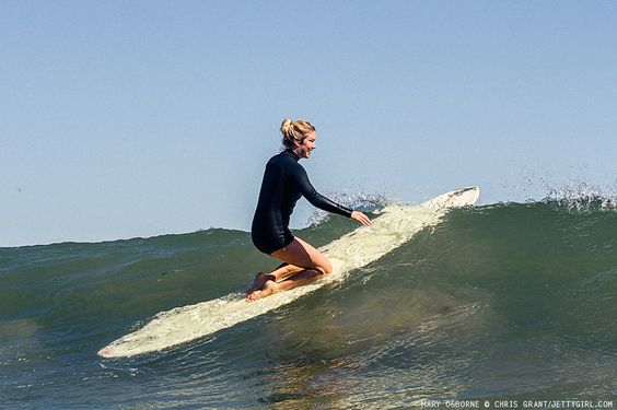 Mary Osborne glides effortlessly up and over a glassy wave. Surf photo by Chris Grant, Jettygirl Surf Mag.