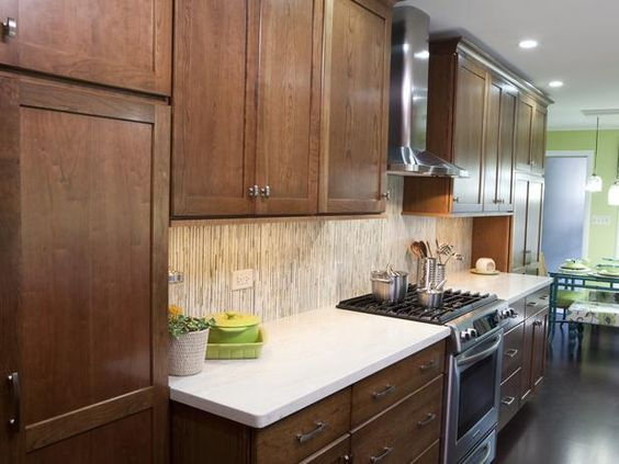 Warm brown cabinets are paired with clean white countertops for a ...