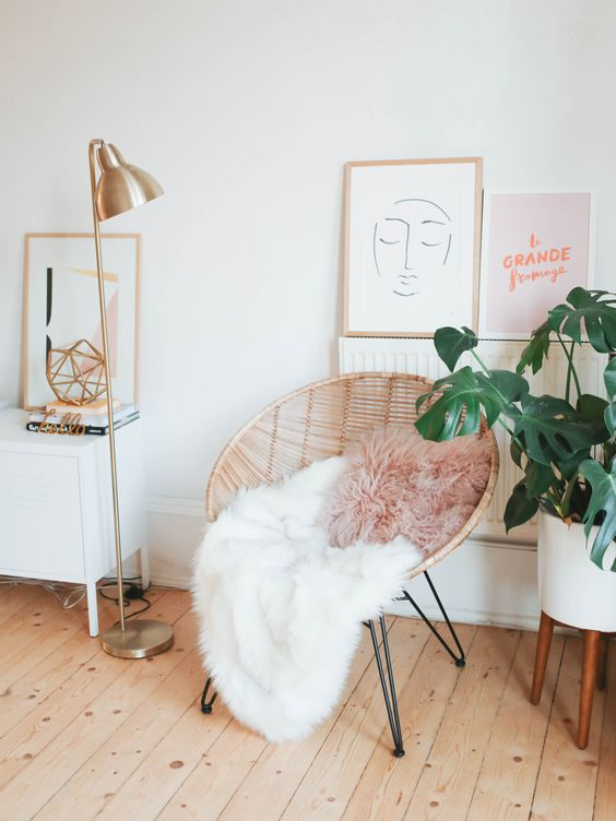 Pops of blush, gold accents, and a bohemian aesthetic all come together to create this relaxing living room corner. See the full artsy room interior to get ideas for redecorating your home with the same light and airy feel.