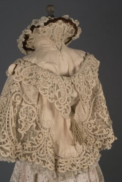 Evening cape, Doucet, ca. 1895-98. Cream-colored wool openwork scrolls with braid and applications of gold-colored muslin. Medici collar and false hood of the burnoose type trimmed with fringes.