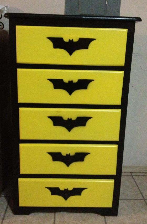 HOLY SHIT NO WAY. The piece of furniture was unfinished. I sanded and then applied a coat of primer to all pieces. The painted the cabinet black and drawers yellow. I purchased a piece of thick cardboard and made a stencil of the batman symbol using an exacto knife. The last steps were to spray paint the logo onto the draw using the stencil, and then applying a clear coat to protect the finish.