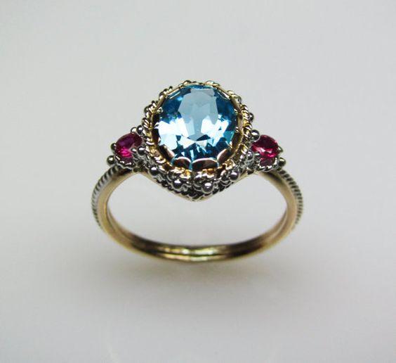 ДИЗАЙН ПОДРОБНОСТИ: Синият Topaz & Ruby пръстен е изцяло ръчно изработен от рециклирано 14 К жълто и бяло злато.  Той се отличава с 9X7 мм син топаз като