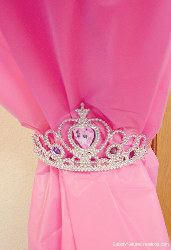 Make a curtain with pink tablecloths, then tie them back with tiaras.  Get supplies at Flower Factory - www.flowerfactory.com: