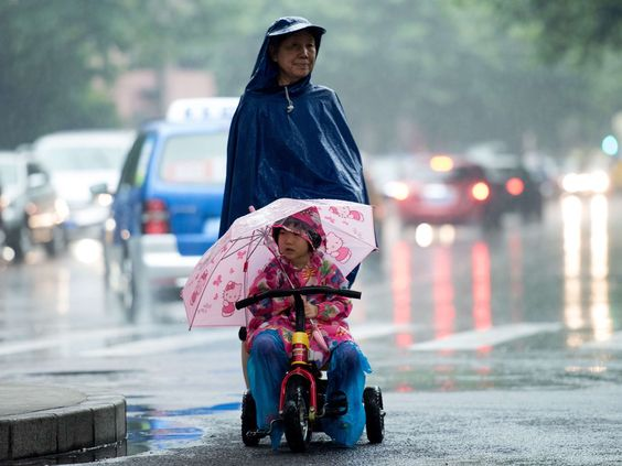 A woman pushes a child on a tricycle through heavy rain in Shanghai.  Johannes Eisele, AFP/Getty Images