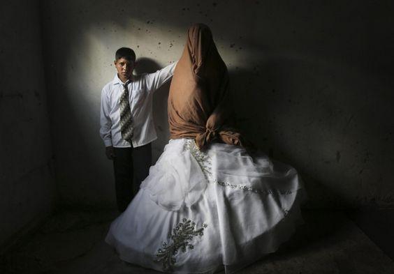 Tala, 14 anni, e Ahmed, 15, celebrano il loro matrimonio a Beit Lahia, nel nord della striscia di Gaza. Ahmed, protagonista del reportage, festeggia con la sua famiglia e tiene per mano Tala, completamente coperta dal velo e dall'abito. La casa della giovane sposa, dove i ragazzi posano per le fotog