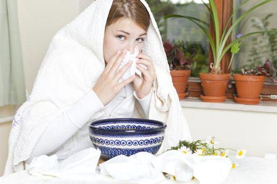 Frau mit Handtuch über Kopf über Schüssel zum Inhalieren