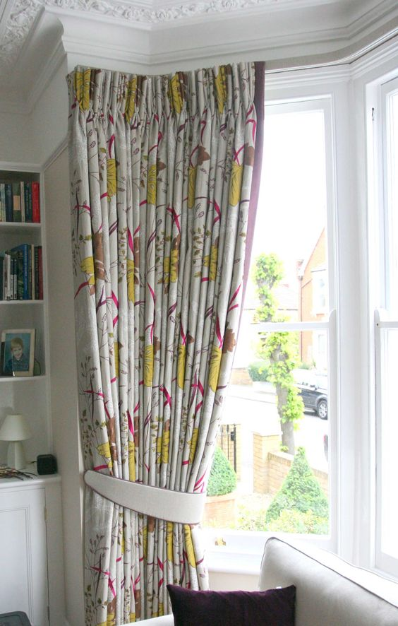 Bay window: embroidered linen curtains (Nina Campbell Syvana Arboretum) with triple pinch pleats , lined and interlined on fabric covered lath: