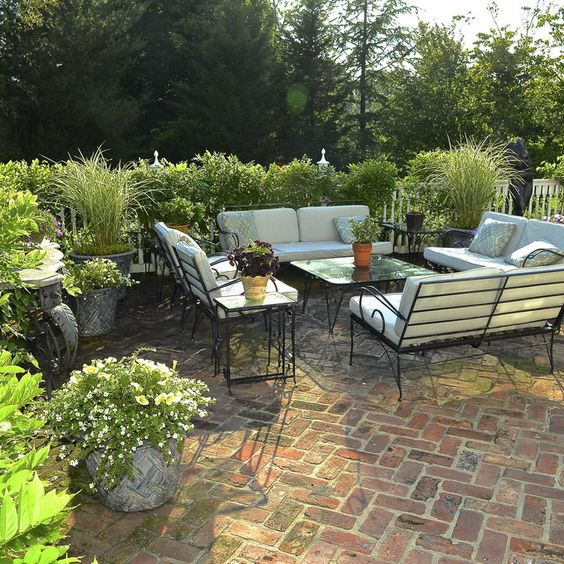 Herringbone brick patio with black iron furniture.: