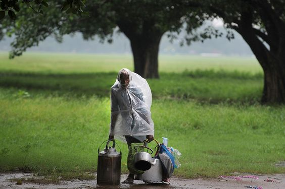 A tea vendor, covered with a plastic sheet for protection from the rain, waited for customers in Kolkata Tuesday. (Dibyangshu Sarkar/Agence France-Presse/Getty Images)