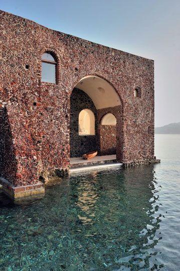 Au ras de l'eau, une maison de cendre et de braise, indécelable de loin tant elle est sculptée dans la matière même de Thirassia, l'îlot volcanique qui se dresse face à sa célèbre voisine, la belle Santorin. L'ancienne darse de débarquement fait office de piscine naturelle.