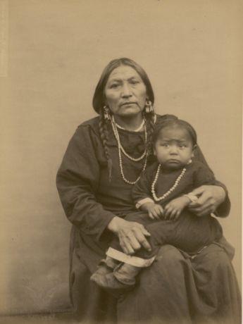 1883 - Omaha (Indiens) | Cook - Nin-daoui. 50 ans ; Femme de Yellow Smoke (Shoudé-Nasi) ; L'enfant qui est photographié avec elle est le fils de Mnigh-di-tai. Il est âgé de 5 ans ; il n'a pas de nom | (Peaux Rouges) / Collection anthropologique du prince Roland Bonaparte