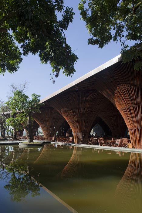Fifteen conical bamboo columns support the roof of this waterside cafe.: