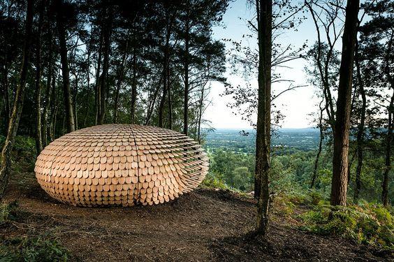 """""""Perspectives"""" est le nom donné par Giles Miller Studio à cet abri de forme organique, niché dans la forêt de Winterfold au sommet de Surrey Hills en Angleterre.  Inspiré par les messages, les initiales et les poèmes gravés sur les bancs publics, les arbres et les cours d'école, Giles Miller les a recueillis et inscrits sur les écailles en cèdre qui forment sa structure.  Ce module fonctionne comme un abri ou un lieu de méditation, il peut également être vu comme une sculpture offerte..."""