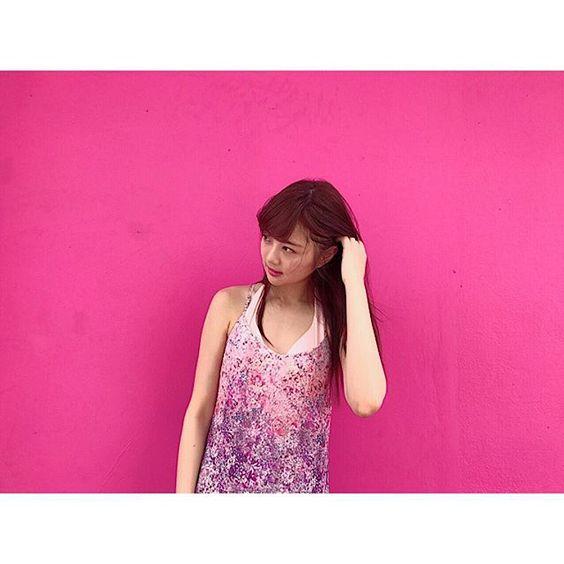 ショッキングピンクの壁をバックにワンピースを着て立っている熊江琉唯の画像