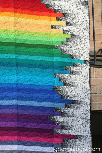 Rainbow Stripe quilt at Gnome Angel.  The clever use of black-and-white gradient fabric at the edges of the strips gives dimension and movement to this quilt.