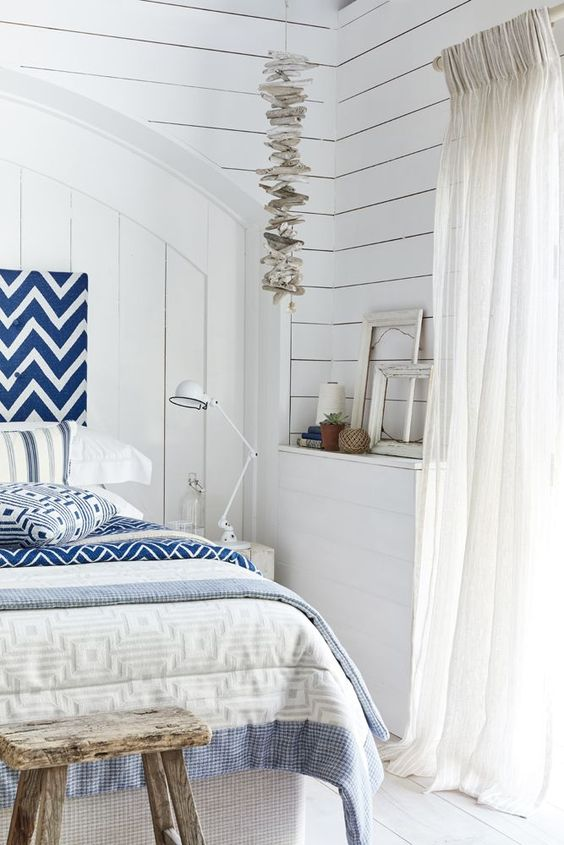 love this blue and white coastal bedroom using linen fabrics by Ian Mankin. Click through for more details and for other coastal and seaside interiors ideas you'll love
