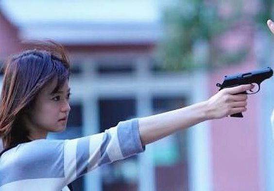 拳銃を構えている鋭い視線をしている小林涼子の画像