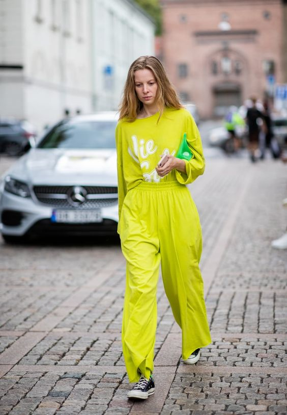 Neon yellow top and pants paired with black converse sneakers.