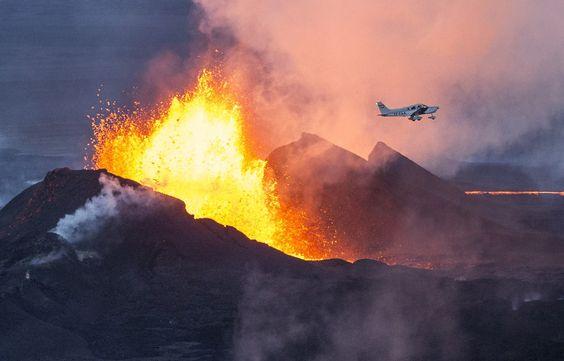 VOLANDO SOBRE UN VOLCAN. Una foto aérea muestra un avión volando sobre el volcán Bardarbunga, arrojando lava y humo en el sureste de Islandia. El sistema volcánico Bardarbunga se ha visto sacudido por cientos de temblores diarios desde mediados de agosto, lo que provocó temores de que el volcán podría explotar. Bardarbunga, a 2.000 m, es el 2° pico más alto de Islandia y se encuentra bajo el glaciar más grande de Europa, Vatnajoekull. (AFP/Bernardo Meric).