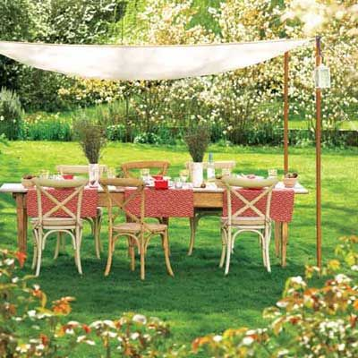 Drape fabric between four poles sunk in the ground for a DIY sunshade. Use tent pins to anchor lines that run from the pole tops to the lawn.