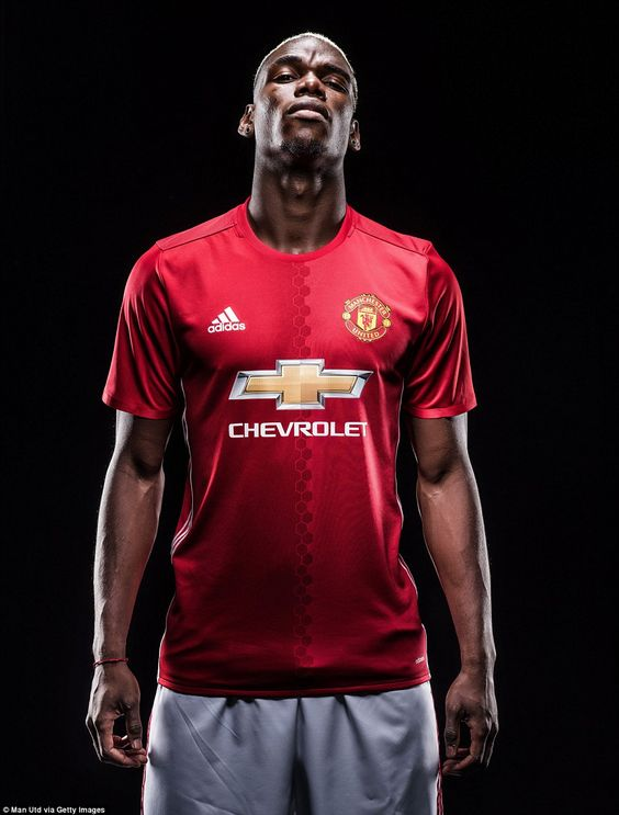Paul Pogba poses in a Manchester United shirt for the first time since returning after com...