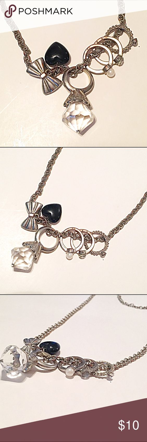 📿Bling & Ring Charm Necklace Silver tone chain necklace featuring a black heart, silver bow, a textured silver ring with clear rhinestone, a smooth silver ring with clear rhinestone, a smooth silver ring with with white faux pearl, and a silver ring with giant clear faceted stone. The rings are removable and a size 6. There is discoloration showing on the silver, but you really can only see it up close. Jewelry Necklaces