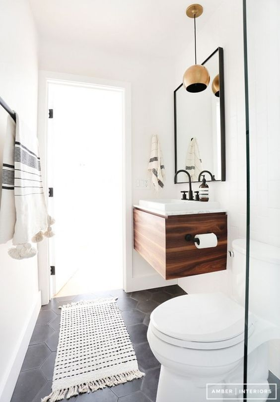 Magnifique petite salle de bain avec tapis, élément en bois, grand miroir et suspension en cuivre.  34 Idées De Petites Salles de Bains : http://www.homelisty.com/petite-salle-de-bain-34-photos-idees-inspirations/